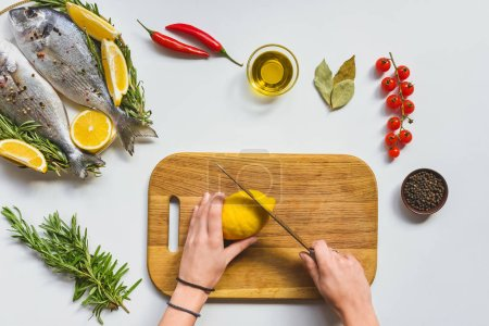 partial view of woman cutting lemon by knife on wooden board near raw fish on table