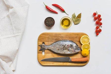 Foto de Vista elevada de pescado crudo y varios ingredientes en mesa blanca - Imagen libre de derechos