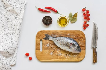 flat lay with uncooked fish on wooden board and various ingredients on white table
