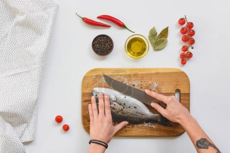 cropped image of tattooed woman cutting fish by knife on wooden board near ingredients on table