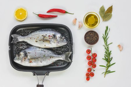 flat lay with various ingredients, uncooked fish decorated by lemon and cherry tomatoes in baking tray