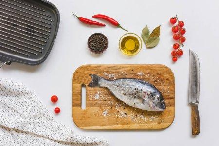 Foto de Vista superior de tomates cherry, aceite de oliva y pescado sin cocinar sobre plancha de madera - Imagen libre de derechos