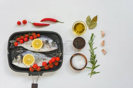 Photo for Elevated view of ingredients, uncooked fish decorated by lemon and cherry tomatoes in baking tray on white table - Royalty Free Image