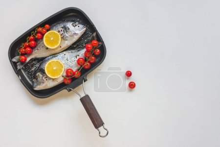 top view of uncooked fish decorated by lemon and cherry tomatoes in baking tray