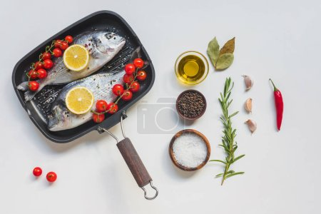 Photo for View from above various ingredients, uncooked fish decorated by lemon and cherry tomatoes in baking tray - Royalty Free Image