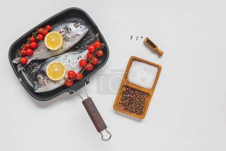 Photo pour Vue de dessus du poisson cru décoré par le citron et les tomates cerises en plateau de cuisson sur blanc table - image libre de droit