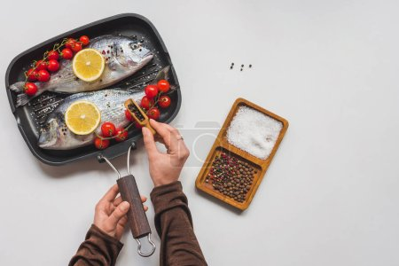 Photo for Partial view of woman peppering uncooked fish and ingredients in tray - Royalty Free Image