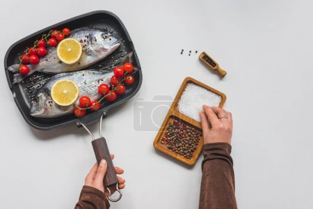 cropped image of woman taking salt at table with uncooked fish and ingredients in tray
