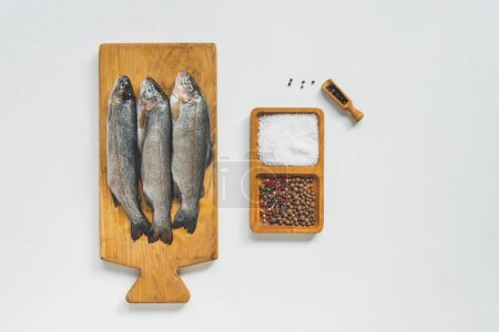Photo for View from above of uncooked fish on wooden board near salt and pepper on white table - Royalty Free Image