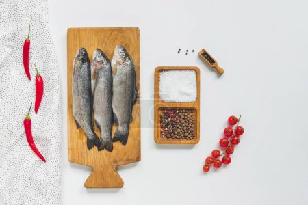 Photo for Top view of uncooked fish on wooden board near ingredients on white table - Royalty Free Image