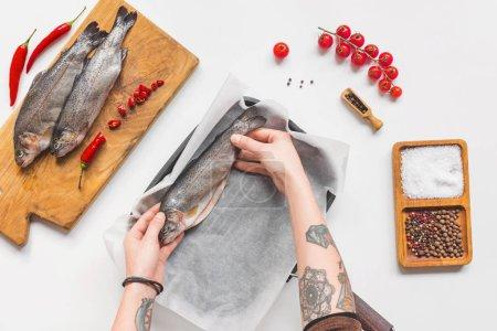 Photo pour Vue partielle de la femme mettant de poissons non cuits dans le bac à papier sur une table blanche avec des ingrédients de cuisson - image libre de droit