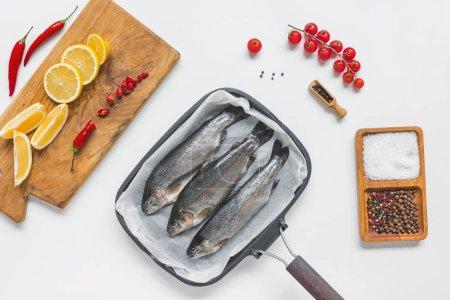 Foto de Vista superior de los peces en hornear bandeja rodeada de varios ingredientes en mesa blanca - Imagen libre de derechos