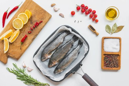 Photo for View from above of fish in baking tray surrounded by various ingredients on white table - Royalty Free Image