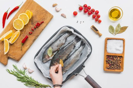 cropped image of woman putting bay leaf on uncooked fish in baking tray on table with ingredients