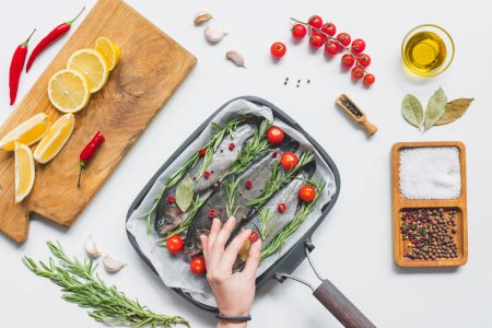 partial view of woman decorating fish in tray with baking paper by cherry tomatoes on table with ingredients