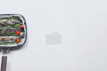 elevated view of fish with rosemary, bay leaves and cherry tomatoes in tray with baking paper on white table