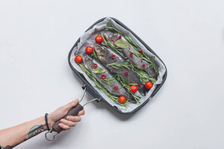 Photo for Cropped image woman holding tray with fish with rosemary, bay leaves and cherry tomatoes over white table - Royalty Free Image