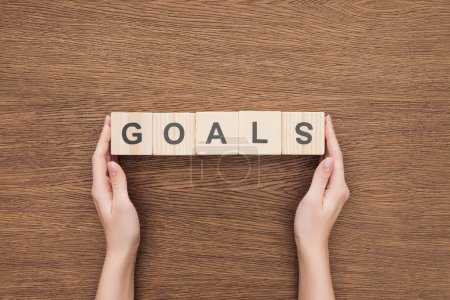 partial view of person holding 'goals' word made of wooden blocks on wooden tabletop, goal setting concept