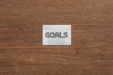top view of 'goals' lettering on card with wooden background
