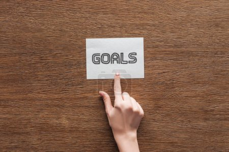 Photo for Partial view of woman pointing at  'goals' lettering on card with wooden background - Royalty Free Image