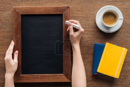 cropped view of woman writing with chalk on blank wooden board