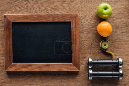 top view of blank wooden chalk board, fruits, dumbbells and measuring tape, dieting and healthy lifesyle concept