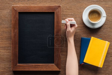 Photo for Cropped view of woman writing with chalk on blank wooden board - Royalty Free Image