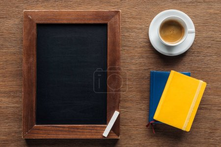 Top view of chalk board with notebooks and coffee on wooden background