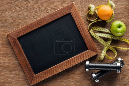 Photo for Top view of blank wooden chalk board, fruits, dumbbells and measuring tape, dieting and healthy lifesyle concept - Royalty Free Image