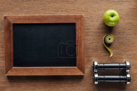top view of blank wooden chalk board, apple, dumbbells and measuring tape, dieting and healthy lifesyle concept