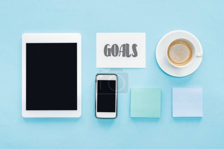 organized flat lay of digital tablet and smartphone with blank screens, sticky notes and 'goals' lettering on card with blue background