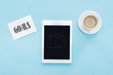 top view of digital tablet with blank screen, 'goals' lettering on card and coffee with blue background