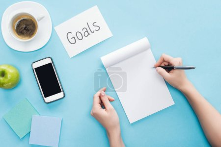 cropped view of woman writing in notebook, lettering 'goals' on card, coffee, sticky notes and smartphone with blank screen on blue background