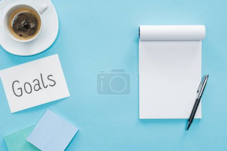 top view of card with 'goals' lettering, blank notebook and cup of coffee on blue background, goal setting concept