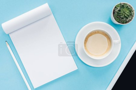 top view of blank notebook with pencil, cup of coffee on blue background
