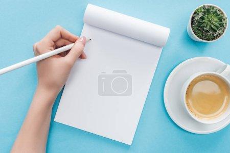 Foto de Recorta la vista de la persona que escribe en el cuaderno en blanco con taza de café sobre fondo azul - Imagen libre de derechos