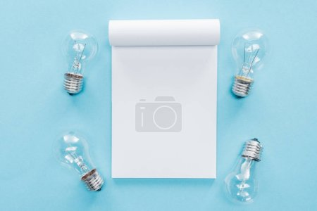 top view of blank notebook with light bulbs on blue background, brainstorming and having idea concept