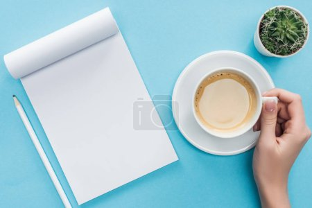 Photo for Cropped view of person holding cup of coffee, blank notebook and pencil on blue background - Royalty Free Image