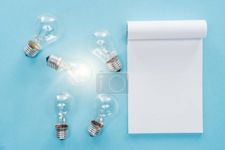 top view of blank notebook with light bulbs on blue background, having new idea concept