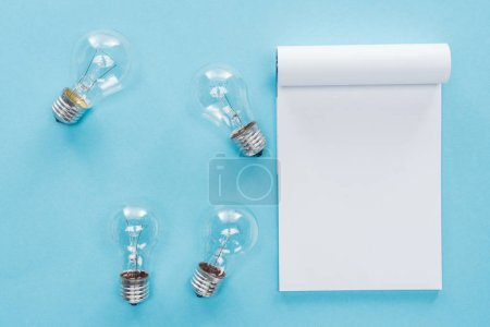 top view of blank notebook with light bulbs on blue background, having idea concept