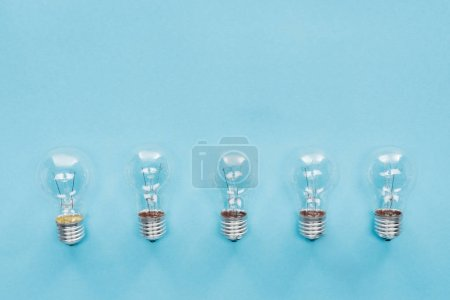 top view of light bulbs in row on blue background, having new idea concept