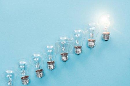 Photo pour Vue de dessus des ampoules dans la rangée et l'un d'eux rayonnant sur fond bleu, ayant un nouveau concept d'idée - image libre de droit