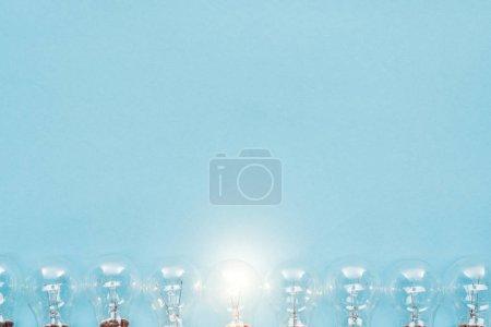 Foto de Vista superior de las bombillas en fila y una de ellas brillando sobre fondo azul, con nuevo concepto de idea - Imagen libre de derechos