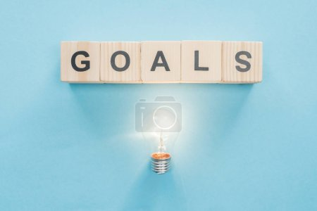 top view of glowing light bulb under 'goals' word made of wooden blocks on blue background, goal setting concept