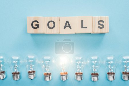 top view of glowing light bulbs under 'goals' word made of wooden blocks on blue background, goal setting concept