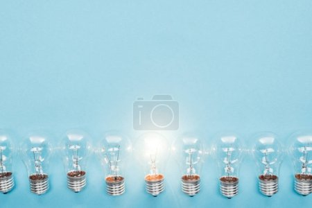 top view of light bulbs in row and one of them glowing on blue background, having new ideas concept
