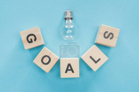 top view of light bulb over 'goals' word made of wooden blocks on blue background, goal setting concept