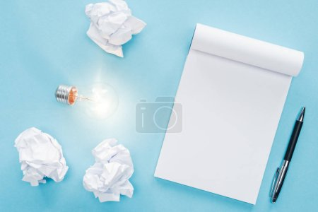 top view of blank notebook with crumbled paper balls and glowing light bulb on blue background, having new ideas concept