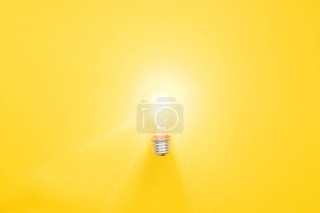 Photo for Glowing light bulb on yellow background, having new ideas concept - Royalty Free Image
