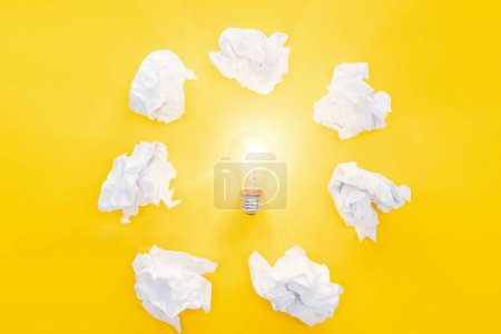 Photo for Glowing light bulb in circle of crumbled paper balls on yellow background, having new ideas concept - Royalty Free Image